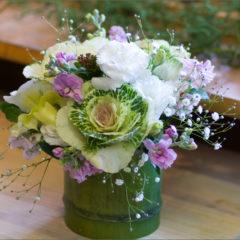 竹の器に淡い色合いでお悔やみの花